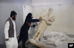 FILE - A five-minute video from the Islamic State group purports to show militants destroying ancient artifacts in Iraq's Mosul Museum. It was released Feb. 26, 2015.
