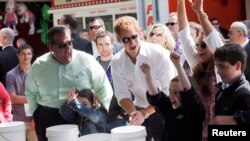 Britain's Prince Harry and New Jersey Governor Chris Christie (L) react as Taylor Cirigliano, 11, of Middletown wins a prize playing the Ball Toss game on the boardwalk in Seaside Heights, May 14, 2013.