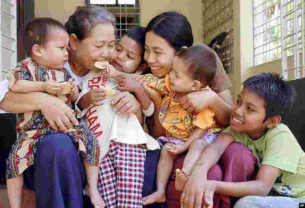 Myanmar orphans infected with the HIV virus are seen together with a caregiver (2nd L), a retire nurse, at a care center for the Happy Heaven Humanitarian Project in Thalyin, near Yangon, File January 24, 2006, (AFP).