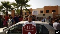 """A demonstrator holds a sign that reads """"Stop evictions,"""" outside a townhouse during a protest to stop the eviction of a family in Torre del Mar, near Malaga southern Spain, June 29, 2011"""