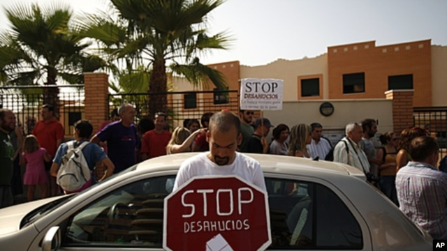 "A demonstrator holds a sign that reads ""Stop evictions,"" outside a townhouse during a protest to stop the eviction of a family in Torre del Mar, near Malaga southern Spain, June 29, 2011"
