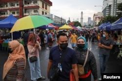 Para pengunjung mengenakan masker saat berbelanja makanan untuk berbuka puasa di pasar Ramadhan, di tengah pandemi COVID-19, di Kuala Lumpur, Malaysia, 15 April 2021. (REUTERS / Lim Huey Teng)