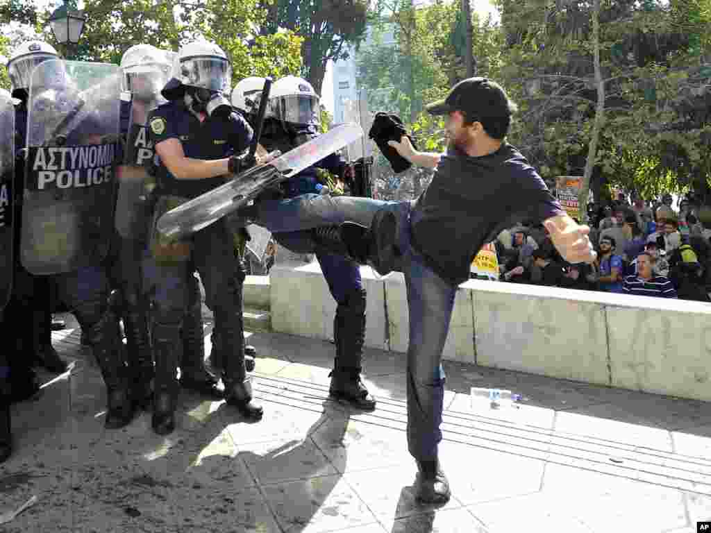 A protester clashes with riot police during a 24-hour nationwide general strike in Athens, Greece, October 18, 2012.