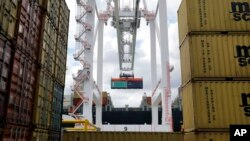 FILE - A crane removes a container from a ship at the Port of Baltimore's Seagirt Marine Terminal in Baltimore, Maryland.