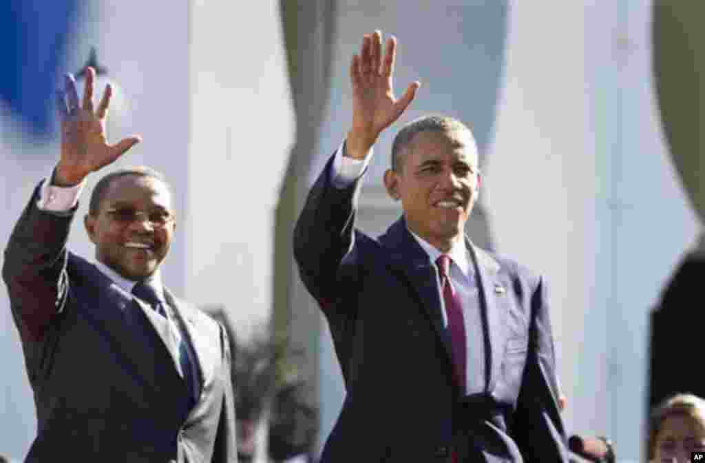 U.S. President Barack Obama, right, and Tanzanian President Jakaya Kikwete, left, wave as they enter State House, in Dar es Salaam, Tanzania Monday, July 1, 2013. Teeming crowds and blaring horns welcomed President Barack Obama to Tanzania's largest city