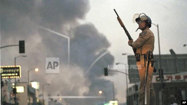一名加州公路巡警在洛杉矶第九街和佛蒙特州大道站岗,大火中升起浓烟。这是洛杉矶骚乱的第二天,此前罗德尼·金(Rodney King)殴打案中的四名洛杉矶警察被无罪释放。(1992年4月30日)(美联社图片 )