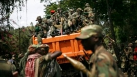 FILE - M23 rebels sit in a vehicle as they withdraw from the eastern Congo town of Goma, Dec. 1, 2012..