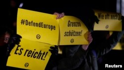 FILE - Demonstrators hold placards with the logo of the far right Identitarian movement during a demonstration against German Chancellor Angela Merkel's migrant policy in Berlin, December 21, 2016.