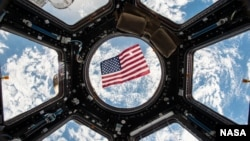 An American flag is visible in the windows of the cupola aboard the International Space Station. Thanks to a bill passed by Texas legislators in 1997 that put in place technical voting procedure for astronauts – nearly all of whom live in Texas – they hav