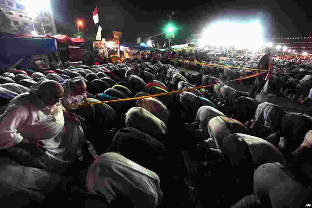 Supporters of ousted president Mohamed Morsi perform evening prayers during their open sit in outside Rabaa al-Adawiya mosque in Cairo, July 30, 2013.