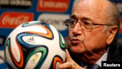 FIFA President Sepp Blatter holds an official 2014 FIFA World Cup soccer ball during a media conference in Sao Paulo, Brazil, June 5, 2014.