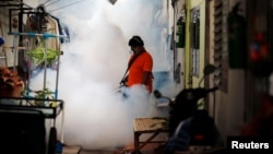 A city worker fumigates the area to control the spread of mosquitoes at a university in Bangkok, Thailand, Sept. 13, 2016.