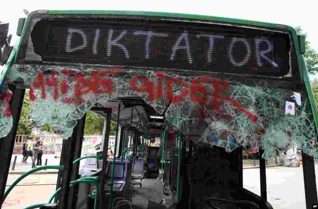 People observe a destroyed urban bus with a destination sign that reads ''This bus goes to Dictator'' at Taksim Square, Istanbul, June 6, 2013.