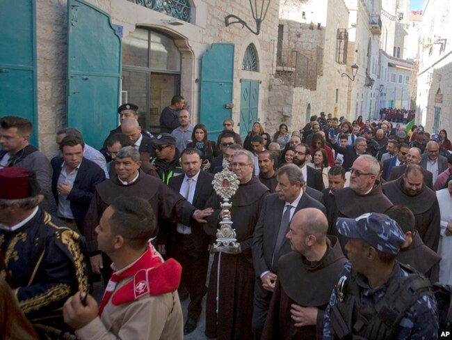 Christian clergymen carry a wooden relic believed to be from Jesus' manger outside the Church of the Nativity, traditionally believed by Christians to be the birthplace of Jesus Christ, in the West Bank city of Bethlehem, Saturday, Nov. 30, 2019.