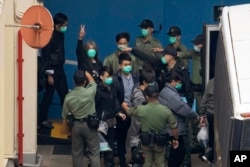 """FILE - Former lawmaker Leung Kwok-hung, known as """"Long Hair,"""" second left, shows a victory sign as some of the 47 pro-democracy activists are escorted by Correctional Services officers to a prison van in Hong Kong, Thursday, March 4, 2021."""