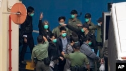 """Former lawmaker Leung Kwok-hung, known as """"Long Hair,"""" second left, shows a victory sign as some of the 47 pro-democracy activists are escorted by Correctional Services officers to a prison van in Hong Kong, Thursday,"""