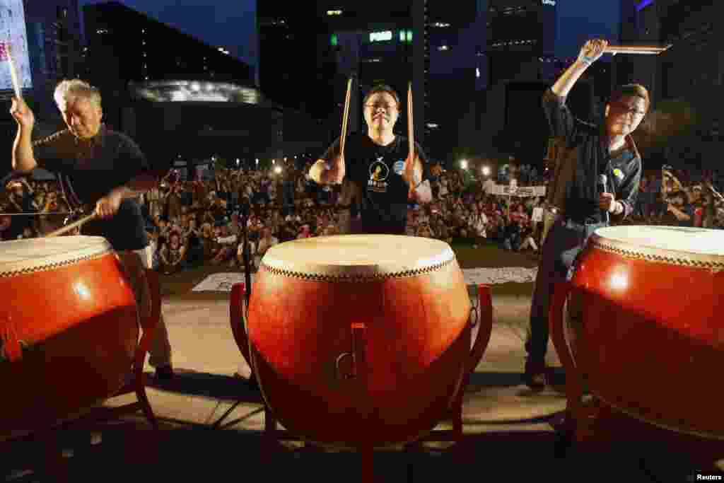 Founders of the Occupy Central civil disobedience movement (L-R), Reverend Chu Yiu-ming, academic Benny Tai and academic Chan Kin-man, hit drums during a campaign to kick off the movement in front of the financial Central district in Hong Kong, Aug. 31, 2014.