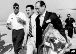 In this April 12, 1975, file photo, U.S. Ambassador to Cambodia John Gunther Dean carries the American flag from the U.S. Embassy in Cambodia as he arrives at Utapao Air Force Base in Thailand following the evacuation from Phnom Penh.