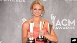 Miranda Lambert poses in the press room with the awards for Vocal Event of the Year, Female Vocalist of the Year and Single Record of the Year at the 49th annual Academy of Country Music Awards at the MGM Grand Garden Arena in Las Vegas, April 6, 2014.