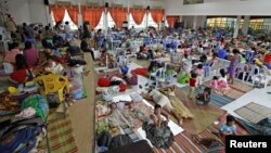 People take shelter from typhoon Hagupit in an evacuation center in Surigao city, southern Philippines, Dec. 5, 2014.