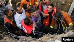 اعضای نهاد دفاع مدنی فلسطینیان در تلاش برای بیرون آوردن یک غیرنظامی از زیر آوار، ۱۸ نوامبر ۲۰۱۲