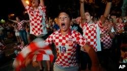 Para pendukung timnas Kroasia merayakan kemenangan timnya dalam adu penalti melawan Rusia, Sabtu (7/7).