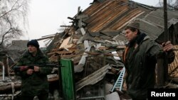 Geopolitical instability, as in eastern Ukraine, could undermine global economic growth, a new U.N. report warns. Here, a pro-Russian rebel and a resident view remnants of a house shelled near Donetsk, Ukraine, Dec. 14, 2014.