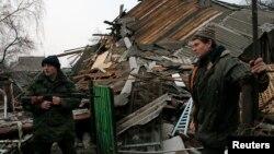 Separatis pro-Rusia dan seorang pria berdiri di sebuah rumah warga di Gorlovka, Ukraina timur yang hancur akibat serangan Ukraina (14/12).