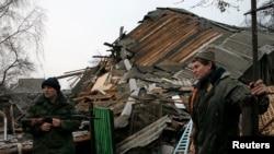 聯合國一份新的報告說,烏克蘭東部等地區的地緣政治動盪因素可能會破壞全球經濟增長。圖為烏東一名親俄分離武裝分子和一位居民在頓涅茨克附近查看被砲擊摧毀的房屋廢墟。