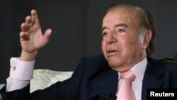 FILE - Former Argentine president Carlos Menem speaks during an interview with Reuters at his home in Buenos Aires, Oct. 6, 2009.
