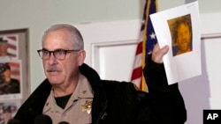 Phil Johnston, the assistant sheriff for Tehama County, Calif., displays a booking photo, from a prior arrest, of Kevin Janson Neal, during a news conference, Nov. 15, 2017, in Rancho Tehama Reserve, Calif. Neal went on a shooting spree Tuesday before being shot and killed by Tehama County sheriff's deputies.