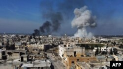 Smoke billows over the town of Saraqib in the eastern part of the Idlib province in northwestern Syria, following bombardment by Syrian government forces, on February 27, 2020-