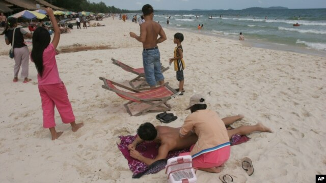 A Cambodian woman gives massage to a tourist on the beach of Sihanoukville, some 185 kilometers (115 miles)  southwest of Phnom Penh, file photo.