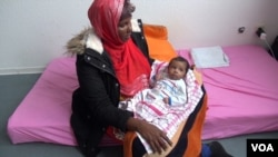 Somali migrant mother Rahma Abukar Ali holds her baby daughter, Sophia, at a refugee center in a small German town near Düsseldorf, where she is awaiting a response to her application for asylum, Oct. 2015. (A. Osman/VOA)