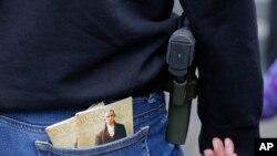Une femme porte une arme en même temps que deux exemplaires de la Constitution américaine lors d'un meeting pro-armes à Olympia, dans l'État de Washington.