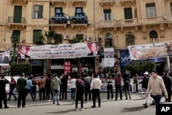 FILE - People hold banners showing support for Egyptian presidential candidates on a street in downtown Cairo, March 4, 2018.