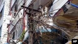 Một cột điện trong thành phố Rangoon, Miến Điện với dây điện chằng chịt. Ngân hàng Thế giới hứa cung cấp 2 tỷ đôla cho vay, viện trợ tặng dữ và đầu tư để giúp Miến Điện cải thiện khu vực năng lượng và y tế