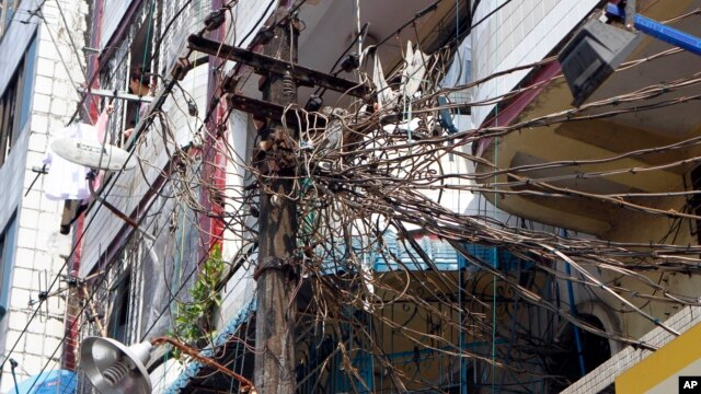 A woman, top left, stands at a balcony of her apartment near a lamp post jumbled with electric cables in Rangoon, Burma, Jan. 27, 2014.