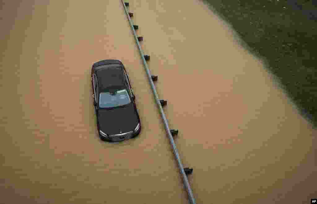 A partially submerged car sits on a flooded section of Interstate 695 in Baltimore, Maryland, USA, after heavy rains fell across the Mid-Atlantic region, Aug. 12, 2014.
