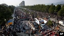 ຜູ້ສະໜັບສະໜຸນ ອາຈານ Tahir-ul Qadri ທໍາການນັ່ງປະທ້ວງ ຢູ່ອ້ອມຕຶກສະພາໃນນະຄອນຫຼວງ Islamabad ບ່ອນທີ່ພວກເຂົາເຈົ້າ ໄດ້ຮຽກຮ້ອງໃຫ້ມີການຍຸບລັດຖະບານ.