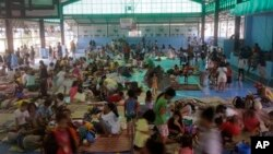 FILE - Residents rest in an evacuation center at suburban Quezon city northeast of Manila, Philippines after fleeing their homes in anticipation of typhoon Hagupit, Dec. 9, 2014.