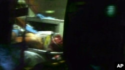 This still frame from video shows Boston Marathon bombing suspect Dzhokhar Tsarnaev visible through an ambulance after he was captured in Watertown, Massachusetts, Apr. 19, 2013.