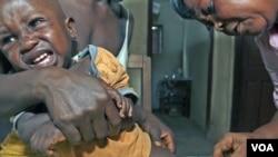 Aliyatu Abdulai (kanan), petugas Klinik Kesehatan Ibu dan Anak di Sierra Leone, sedang memvaksinasi sorang anak di desa Sembehun. Sierra Leone adalah salah satu negara yang mendapat program bantuan pendanaan vaksin dari GAVI.