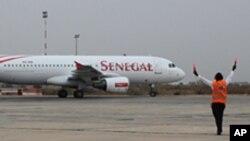 Un contrôleur de l'aéroport dirige un Airbus du Senegal Airlines qui va décoller à Dakar