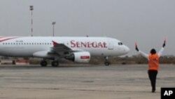 Un aiguilleur de l'air dirige un avion de Senegal Airlines à l'aéroport international de Dakar, Sénégal (archives)