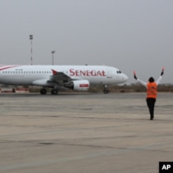 An airport controller directs a Senegal Airlines Airbus at the official launch ceremony for the new airline in Dakar