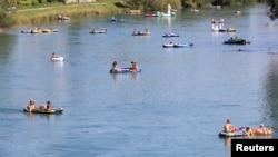 Para pengunjung menikmati musim panas di tengah pandemi virus corona (Covid-19) di Sungai Limmat, Zurich, Swiss, 9 Agustus 2020. (Foto: Reuters)