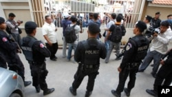 FILE - Cambodian riot police officers stand guard at the main gate of the Phnom Penh Municipal Court, in Phnom Penh, Cambodia, Aug. 15, 2015.