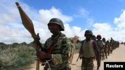 FILE - African Union Mission in Somalia (AMISOM) peacekeepers from Burundi patrol after fighting between insurgents and government soldiers on the outskirts of Mogadishu, May 22, 2012.