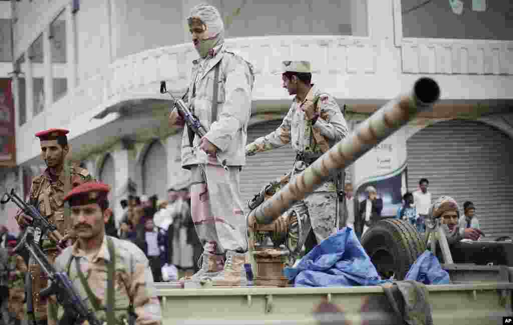 Defected army soldiers stand guard on a vehicle while protesters, unseen, march during a demonstration demanding the prosecution of Yemen's President Ali Abdullah Saleh in Sanaa, Yemen, November 24, 2011. (AP)